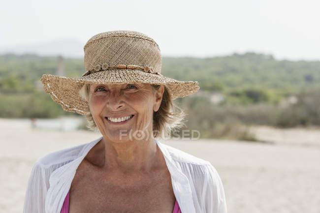 Donna maggiore sorridente con cappello di paglia alla spiaggia che guarda l'obbiettivo — Foto stock