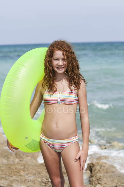 Ragazza con nuotata anello che sta sulla spiaggia — Foto stock