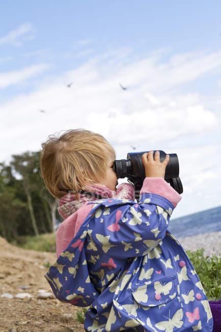 Girl looking through binocular at beach — Stock Photo