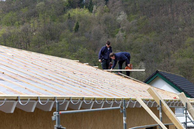 Manual workers placing roof on house — Stock Photo