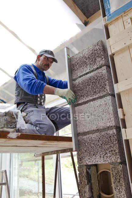 Operaio di sesso maschile che installa isolamento termico in cantiere — Foto stock