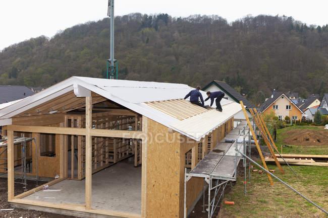 Trabalhadores manuais telhados em casa de madeira — Fotografia de Stock