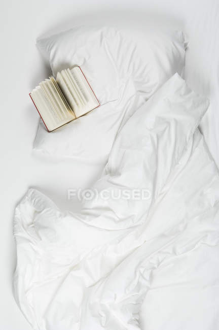 Book on bed with white surface — Stock Photo