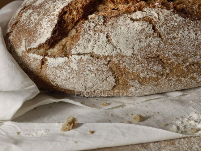 Loaf of bread on textile towel , close up — Stock Photo