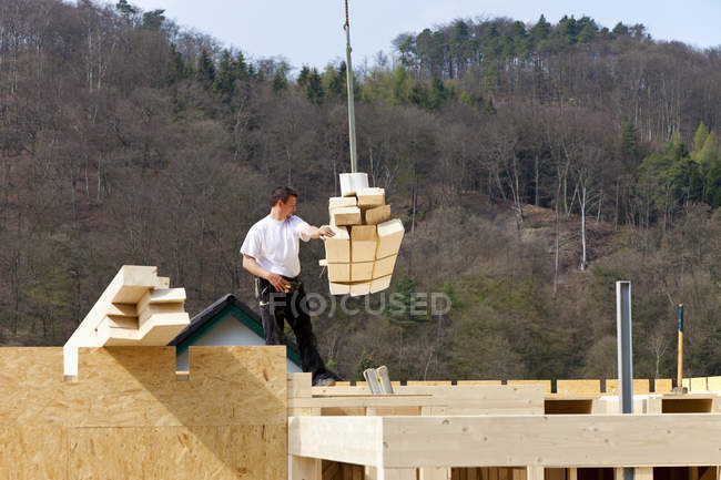 Man installing and fixing wooden walls of prefabricated house — Stock Photo