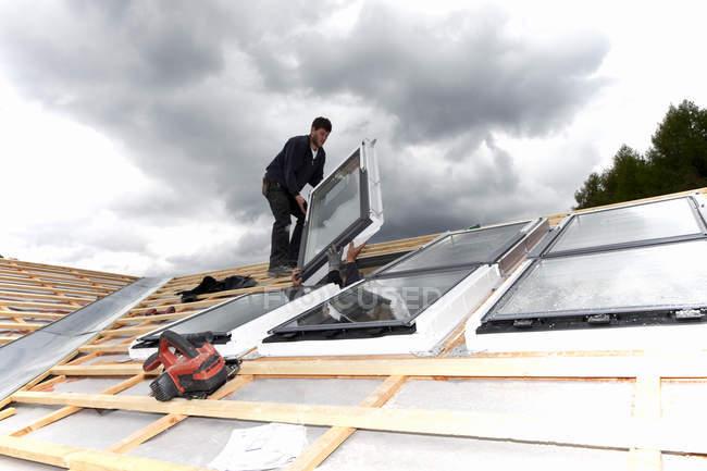 Trabajadores instalando ventanas de techo en obra - foto de stock