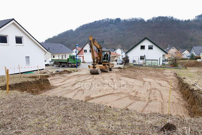 Man preparing ground for house foundation with excavation vehicle — Stock Photo
