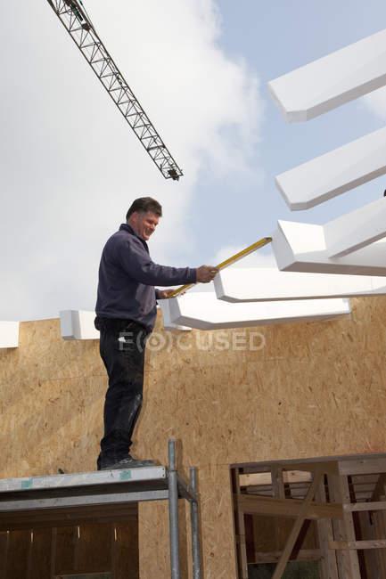 Человек, работающий с уровнем воды на строительной площадке — стоковое фото