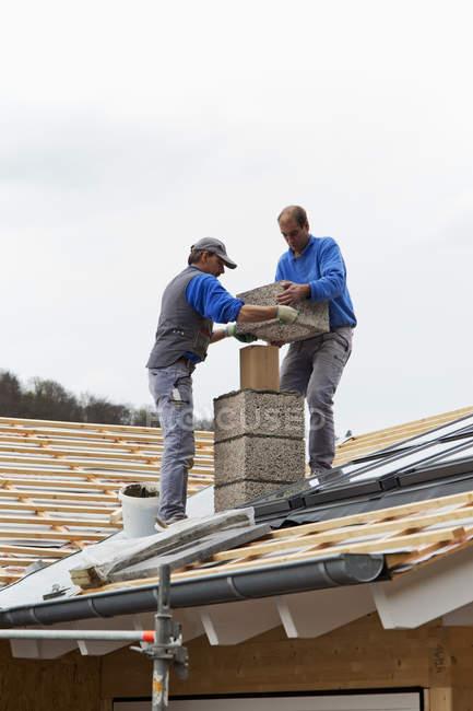 Lavoratori che installano camino sul tetto — Foto stock
