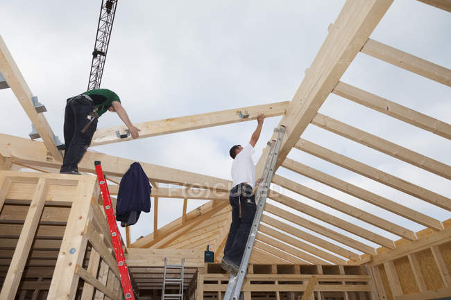 Men working on roof of wooden house — Stock Photo