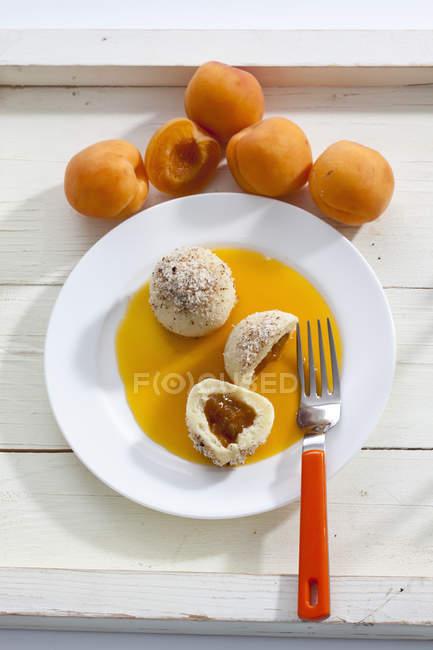 Canederli di albicocche con nocciola con messa a terra sulla piastra e albicocche in background — Foto stock
