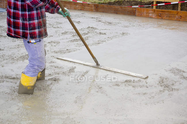 Man smoothing concrete for foundation of house building — Stock Photo