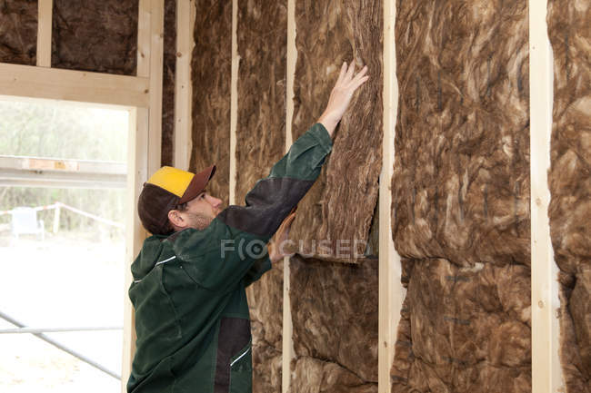 Worker placing thermal felt insulation inside house — Stock Photo