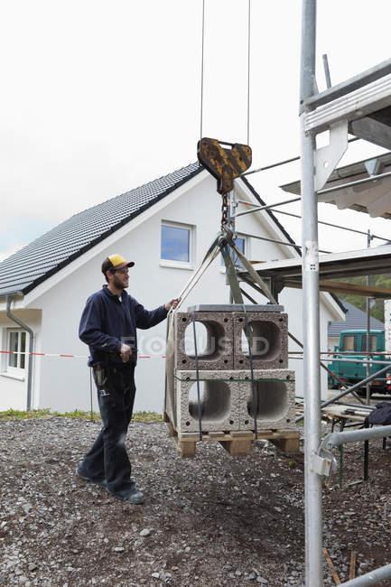 Uomo controllo gru con materiale da costruzione — Foto stock