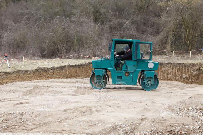 Uomo terra rotolamento con rullo compressore per la costruzione di fondazione casa — Foto stock
