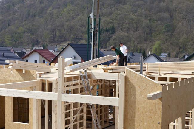 Hommes assemblant crête de toit de maison préfabriquée — Photo de stock