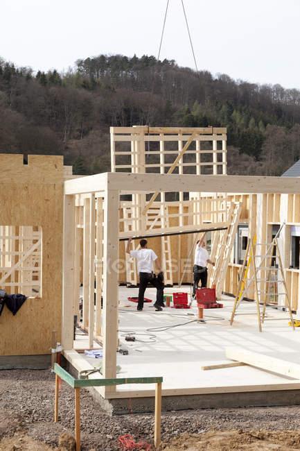 Uomini che installano e fissano pareti in legno di casa prefabbricata — Foto stock