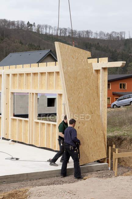 Мужчины устанавливают и фиксируют деревянные стены сборного дома — стоковое фото