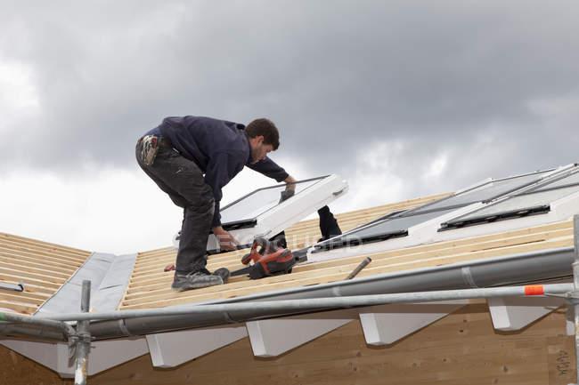 Travailleur installant des fenêtres de toit sur la maison en bois — Photo de stock