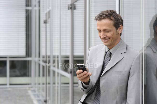 Бізнесмен, за допомогою мобільного, посміхаючись — стокове фото