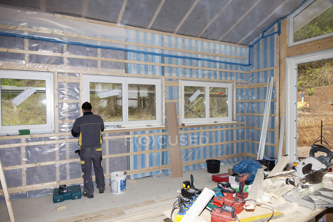 Worker installing vapour barrier in building construction — Stock Photo