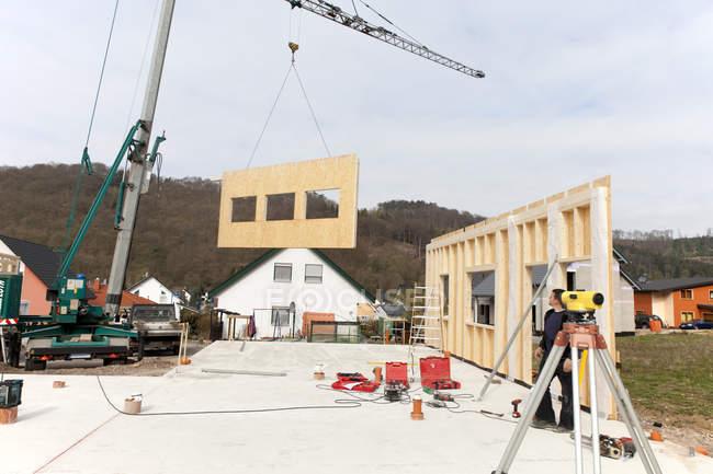 Человек устанавливает и фиксирует деревянные стены сборного дома — стоковое фото