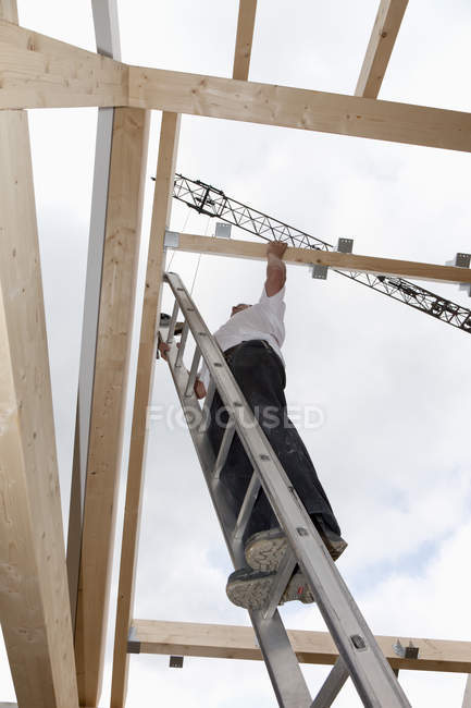 Man working on roof of wooden house — Stock Photo