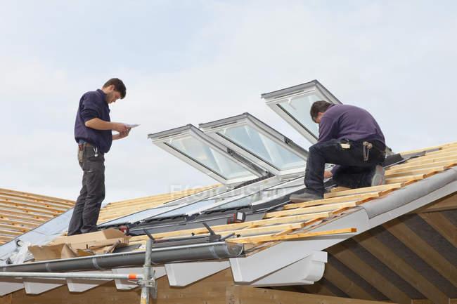 Dos operários instalando janelas de telhado — Fotografia de Stock