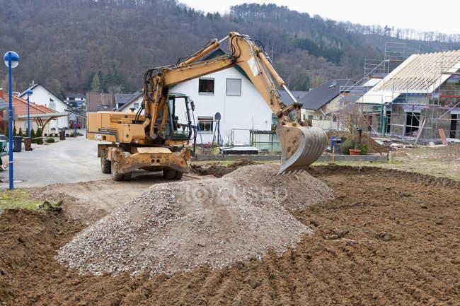Людина в розкопках транспортного засобу готує грунт для Будинок фундаментні — стокове фото
