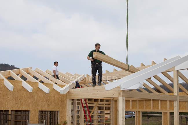 Hombres trabajando en el techo de la concha del edificio - foto de stock