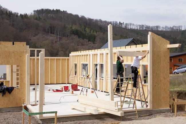 Hombres instalando y fijando paredes de madera de casa prefabricada - foto de stock