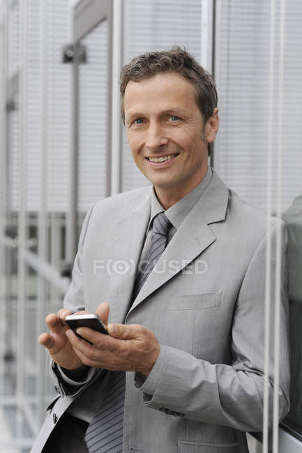 Businessman using mobile, smiling, portrait — Stock Photo