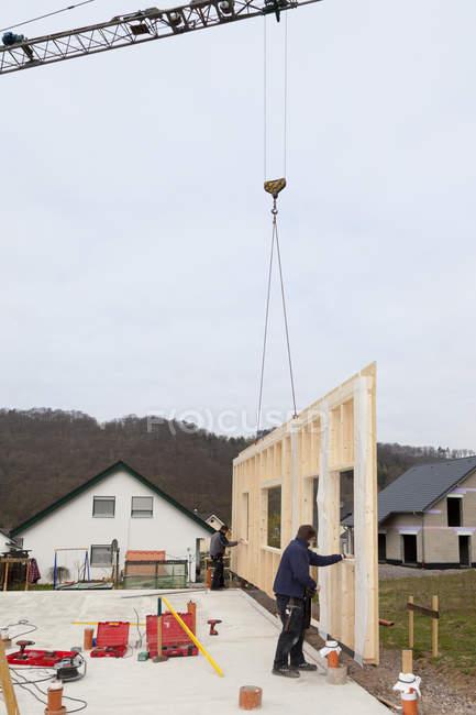 Hommes fixation de la grue pivotant mur de maison préfabriquée sur fondation — Photo de stock