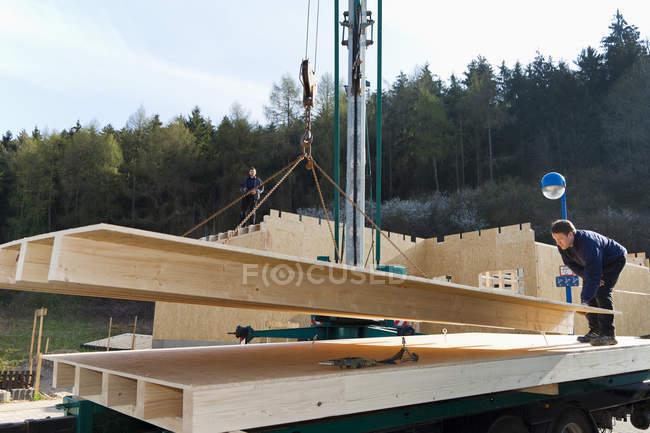Hommes installant et fixant des murs en bois de maison préfabriquée — Photo de stock