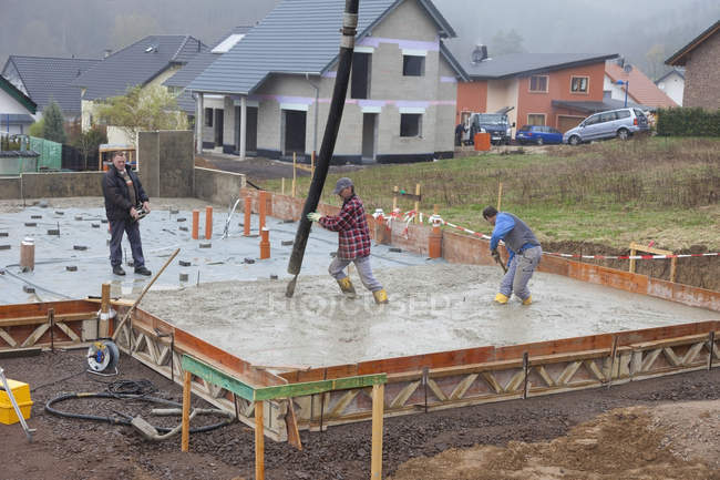 Construction workers filling concrete for foundation and man holding remote control — Stock Photo