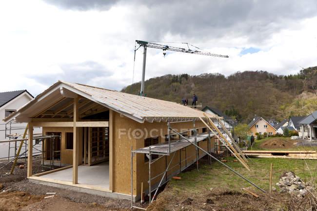 Travailleurs plaçant le toit sur la maison en bois — Photo de stock