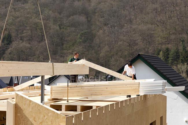 Men assembling ridge purlin of prefabricated house — Stock Photo