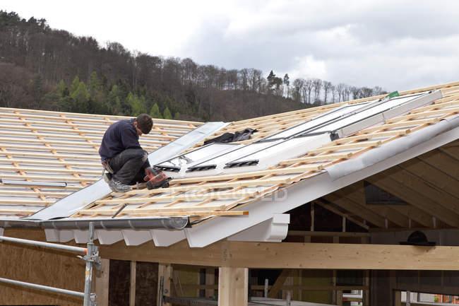 Trabajador instalando ventanas de techo en el sitio de construcción - foto de stock