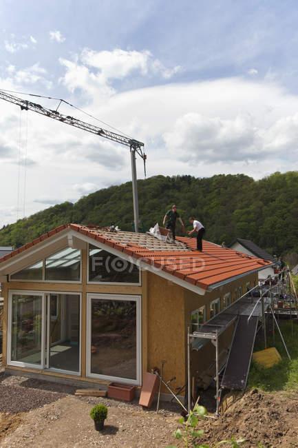 Днем два работника-мужчины строят крышу дома — стоковое фото