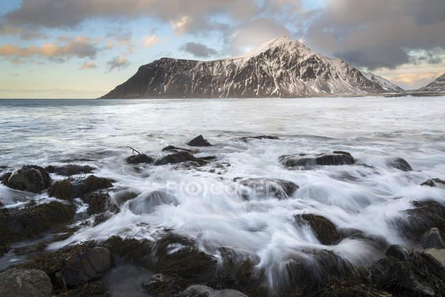 Plage rocheuse Flakstad Norvège, îles Lofoten, au coucher du soleil avec la montagne sur fond — Photo de stock