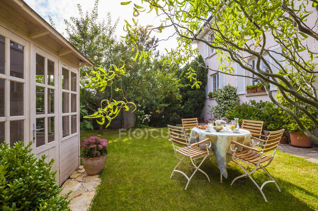 Garden shed and laid table on grassy lawn — Stock Photo