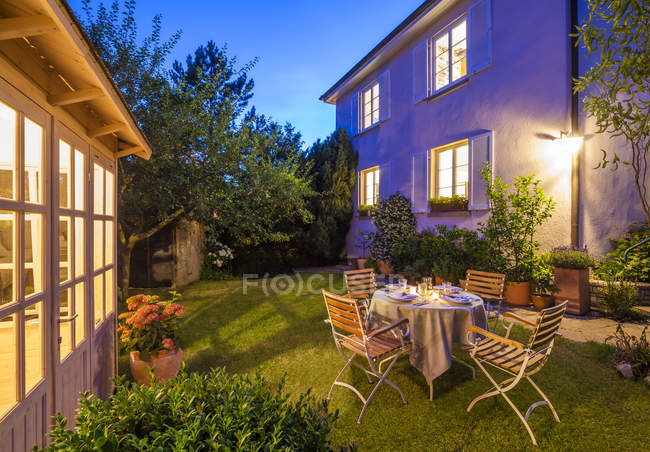 Laid table in garden in the evening lights — Stock Photo