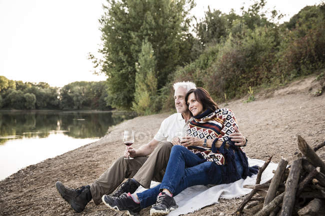 Relaxed senior couple at a lake in the evening — Stock Photo