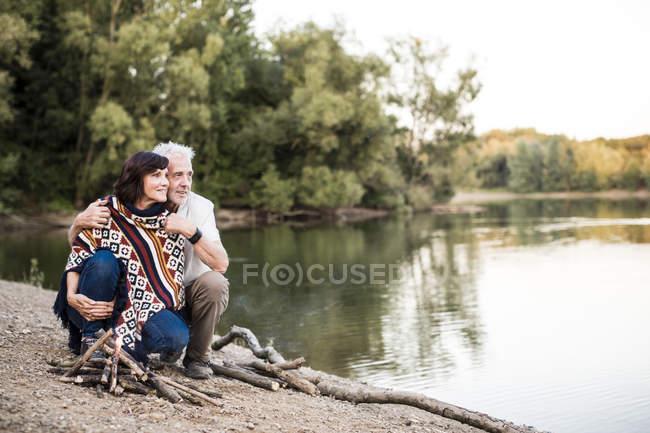 Coppia senior al falò in un lago — Foto stock