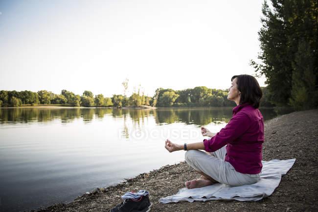 Старшая женщина на озере, практикующая йогу — стоковое фото