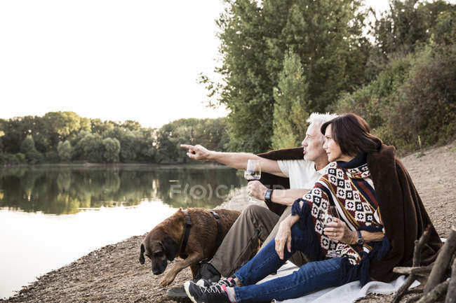 Coppie maggiori con il cane in un lago di sera — Foto stock