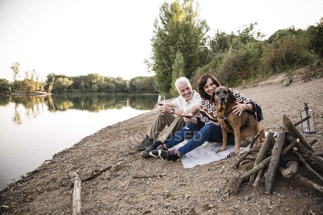 Coppie maggiori felici con il cane in un lago di sera — Foto stock