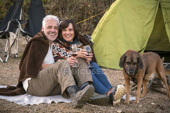Happy senior couple with wine and dog at a tent — Stock Photo