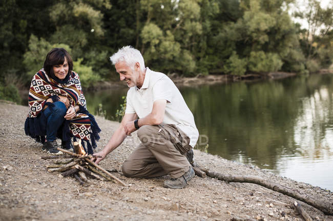 Senior couple lighting a campfire at a lake in the evening — Stock Photo
