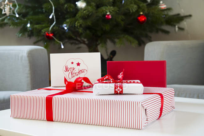 Wrapped Christmas presents near tree — Stock Photo